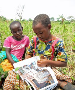 Girls who live in the Kyangwali Refugee Settlement look at a book from the Little Free Library