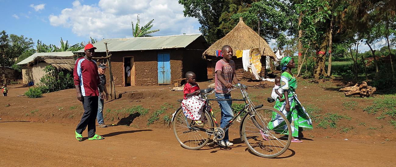 Angela walking, Ruth on bike, Kyangwali (2014, Peopleweaver)